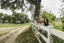 Portrait de couple senior et filles appuyé contre la barrière de ranch, Bridger, Montana, Usa — Photo de stock