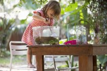 Girl standing on chair to scoop fishing net in plastic aquarium on garden table — Stock Photo