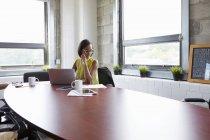 Молодая женщина за столом в конференц-зале — стоковое фото