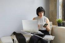 Бізнес-леді за допомогою ноутбука та проведення смартфон — стокове фото
