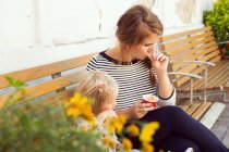 Mother and toddler daughter eating ice cream on park bench — Stock Photo