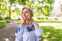 Femme mûre avec la main dans des cheveux blonds, regardant par-dessus l'épaule dans le parc — Photo de stock