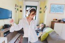 Девушка в наушниках танцует в гостиной — стоковое фото