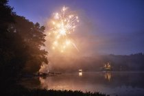 Fogos de artifício explodindo sobre Lago ao entardecer — Fotografia de Stock