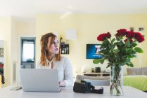 Young woman at living room table looking sideways while using laptop — Stock Photo