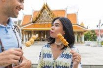 Espetadas de turista jovem casal comendo comida de rua, fora do templo, Bangkok, Tailândia — Fotografia de Stock
