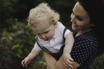 Femme adulte moyenne portant enfant en bas âge fils dans les bras — Photo de stock