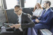 Бизнесмен смотрит на цифровой планшет на пассажирском пароме — стоковое фото