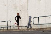 Молодая женщина бегает вдоль бетонной стены — стоковое фото