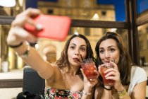Women drinking cocktails taking selfie with smartphone — Stockfoto