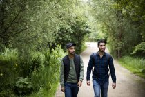 Two friends walking on pathway in park — Stock Photo