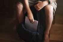 Cropped image of boy packing backpack and putting notebook — Stock Photo