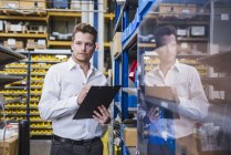 Male factory manager with clipboard in factory warehouse — Stock Photo