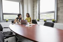 Two women sitting at meeting room table and using laptop — Stock Photo