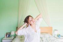 Jeune femme sur lit bâillements et étirements — Photo de stock