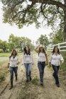 Coppia matura passeggiando con giovani donne lungo la strada sterrata ranch, Bridger, Montana, Stati Uniti d'America — Foto stock