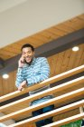 Young businessman making smartphone call on balcony — Stock Photo