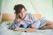 Junge Frau liegt auf dem Bett und liest ein Buch — Stockfoto
