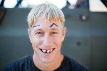 Портрет молодого человека с плохо стриженными волосами, нарисованный на бровях и выбитых зубах — стоковое фото
