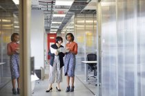 Two businesswomen looking at digital tablet in office corridor — Stock Photo