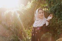 Jovem mulher vestindo no hijab admirando plantas — Fotografia de Stock