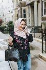 Jeune femme dans le hijab faire un appel téléphonique dans la rue — Photo de stock