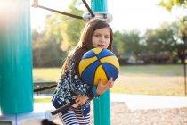 Дівчинка тримає баскетбольний майданчик і посміхається на камеру — стокове фото