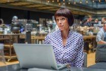 Portrait de femme mature utilisant un ordinateur portable dans un café — Photo de stock
