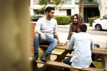 Friends enjoying coffee together on park bench — Stock Photo