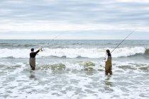 Jovem casal em waders lançando fora varas de pesca — Fotografia de Stock