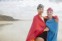Мать и дочь, завернутые в платки на пляже — стоковое фото