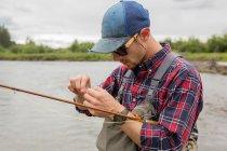Homem preparando isca para pesca com mosca, Clark Fork, Montana — Fotografia de Stock