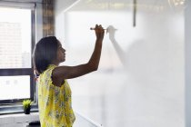 Young woman writing on whiteboard in office environment — Stock Photo
