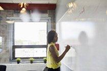 Молодая женщина, писать на доске в среде office — стоковое фото