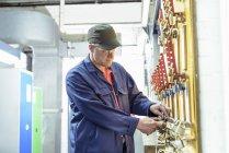 Locomotive engineer inspecting safety padlocks in train works — Stock Photo