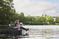 Duas meninas sentadas no molhe e olhando para o lago — Fotografia de Stock