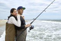 Jovem casal em waders pesca no mar — Fotografia de Stock