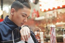 Portrait of Young man talking into smartwatch sitting in diner — Stock Photo