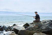 Jovem sentado na pesca do mar de rocha — Fotografia de Stock