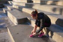 Young woman tying shoelace on training shoe — Stock Photo