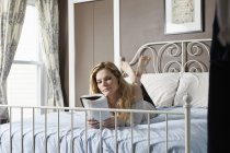 Young woman reading book on bed — Stock Photo