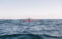 Jovem kayaker mar masculino olhando para o smartphone enquanto pesca, Ilha de Santa Cruz, Califórnia, EUA — Fotografia de Stock
