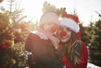 Girl and mother in christmas tree forest with red noses, portrait — Stock Photo