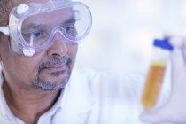 Travailleur de laboratoire examinant une éprouvette remplie de liquide, gros plan — Photo de stock