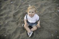 Ritratto del bambino maschio che si siede sulla sabbia — Foto stock
