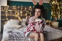 Young woman in christmas jumper sitting on bed — Stock Photo