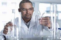 Laborantin mâle choisissant tube de mesure — Photo de stock