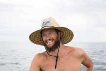 Portrait of smiling Man wearing straw hat against water — Stock Photo