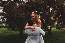 Young man lifting girlfriend in park at dusk — Photo de stock