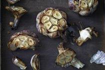 Haut de la page vue des bulbes d'ail rôti sur la table, gros plan — Photo de stock